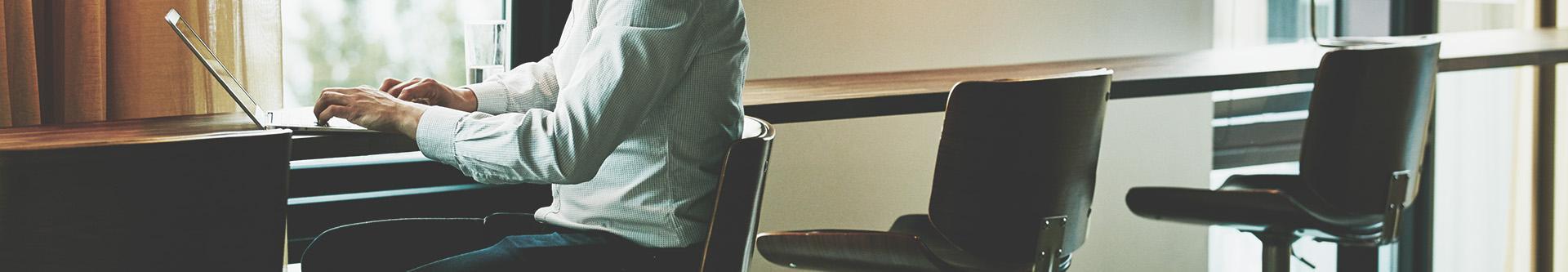 mężczyzna siedzący brzy biurku z laptopem